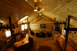 Large open area with with wooden walls, wooden floors, couches, a full kitchen, a fireplace and a large dining table