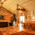 Large open area with with wooden walls, wooden floors, couches, a fireplace and large dining table
