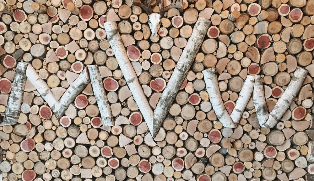 """A wall of wood ends with an """"MVW"""" pattern in wood"""
