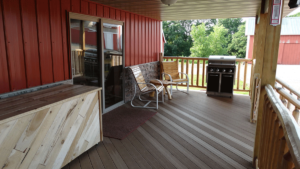 Outdoor, screenless patio with a grill, a table, and chairs