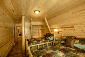 Bedroom with wooden walls, wooden floors, and two beds